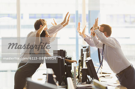 Exuberant business people high-fiving over computers in office Stock Photo - Premium Royalty-Free, Image code: 6113-08549934