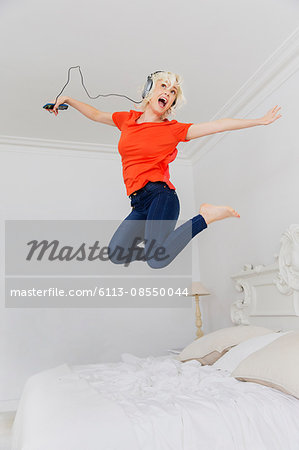 Playful woman jumping on bed listening to music with headphones and mp3 player Stock Photo - Premium Royalty-Free, Image code: 6113-08550044