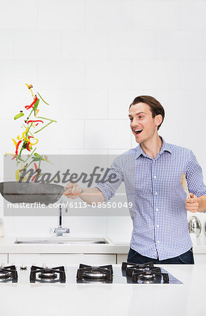 Surprised couple cooking and flipping vegetables in skillet in kitchen Stock Photo - Premium Royalty-Free, Image code: 6113-08550049