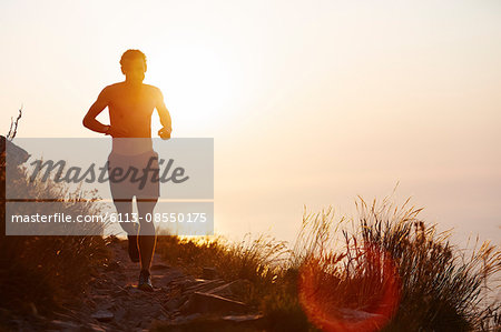 Silhouette of man running on trail with sunset ocean in background