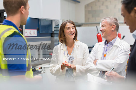 Smiling engineers and managers in steel factory