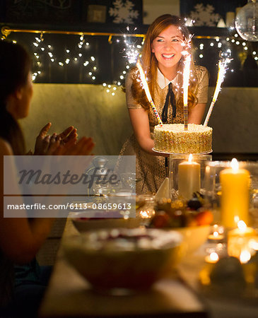 Enthusiastic woman serving cake with sparkler fireworks to clapping friends Stock Photo - Premium Royalty-Free, Image code: 6113-08659613
