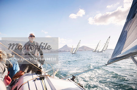 Man adjusting sailboat rigging on sunny ocean Stock Photo - Premium Royalty-Free, Image code: 6113-08698110