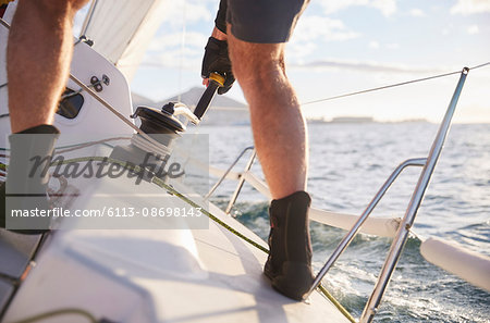 Man sailing turning cable winch on heeling sailboat Stock Photo - Premium Royalty-Free, Image code: 6113-08698143