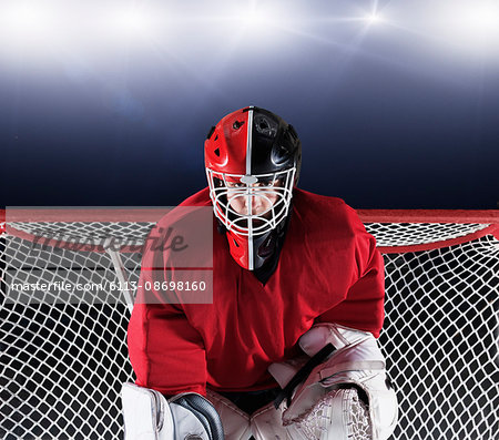 Portrait determined hockey goalie protecting goal net Stock Photo - Premium Royalty-Free, Image code: 6113-08698160