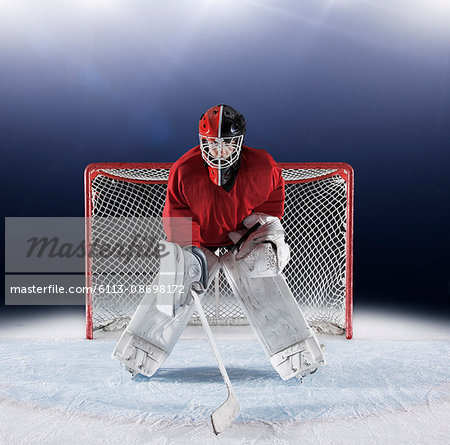 Portrait determined hockey goalie protecting goal net on ice Stock Photo - Premium Royalty-Free, Image code: 6113-08698172