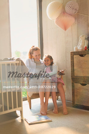 Pregnant mother and daughter reading story book in nursery Stock Photo - Premium Royalty-Free, Image code: 6113-08722029