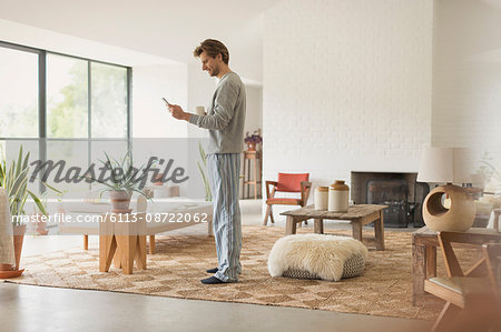 Man in pajamas drinking coffee and using digital tablet in living room Stock Photo - Premium Royalty-Free, Image code: 6113-08722062