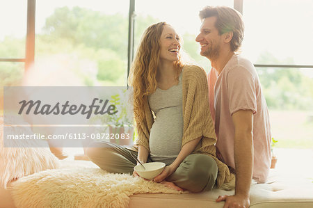 Smiling pregnant couple eating and talking Stock Photo - Premium Royalty-Free, Image code: 6113-08722083