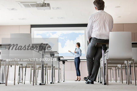 Businessman watching businesswoman leading presentation at projection screen in conference room Stock Photo - Premium Royalty-Free, Image code: 6113-08722123