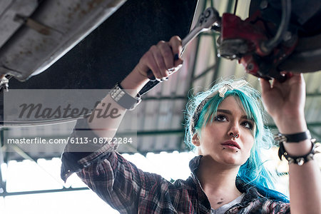 Young female mechanic with blue hair fixing car in auto repair shop Stock Photo - Premium Royalty-Free, Image code: 6113-08722284