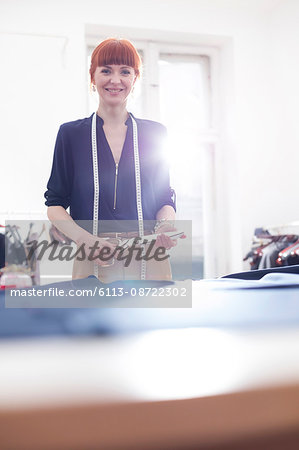 Portrait confident female tailor holding scissors in menswear workshop Stock Photo - Premium Royalty-Free, Image code: 6113-08722302
