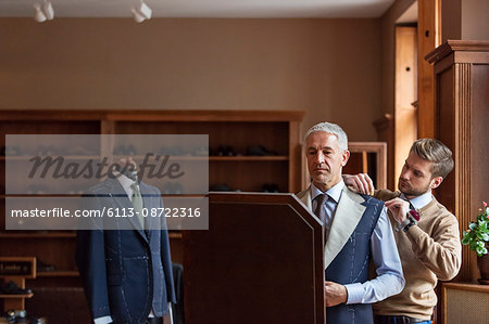 Tailor fitting businessman for suit in menswear shop Stock Photo - Premium Royalty-Free, Image code: 6113-08722316
