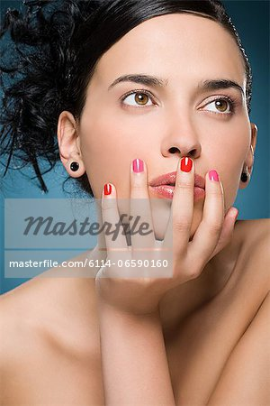 Young woman with hand on face Stock Photo - Premium Royalty-Free, Image code: 6114-06590160