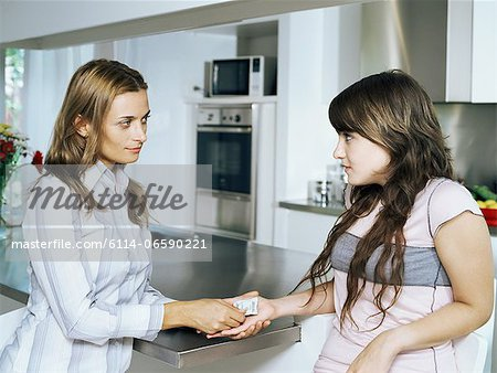 Mother giving condom to daughter Stock Photo - Premium Royalty-Free, Image code: 6114-06590221