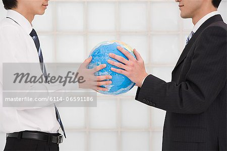 Office workers holding globe Stock Photo - Premium Royalty-Free, Image code: 6114-06591186