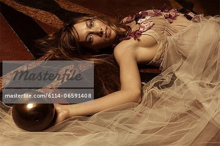 Young woman lying on floor with ball Stock Photo - Premium Royalty-Free, Image code: 6114-06591408