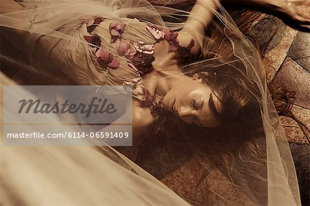 Young woman lying on floor Stock Photo - Premium Royalty-Free, Image code: 6114-06591409