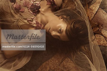 Young woman lying on floor Stock Photo - Premium Royalty-Free, Image code: 6114-06591410
