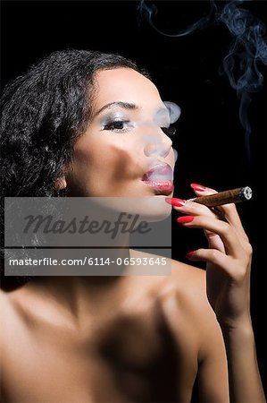 Beautiful woman smoking a cigar Stock Photo - Premium Royalty-Free, Image code: 6114-06593645