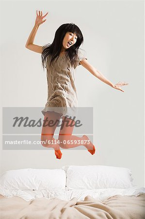 Young woman jumping on bed Stock Photo - Premium Royalty-Free, Image code: 6114-06593873