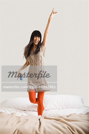Woman dancing on bed Stock Photo - Premium Royalty-Free, Image code: 6114-06593901