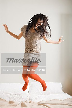 Woman jumping on bed Stock Photo - Premium Royalty-Free, Image code: 6114-06593910