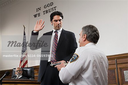A witness swearing an oath Stock Photo - Premium Royalty-Free, Image code: 6114-06593951