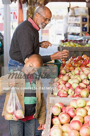 A boy and his grandfather choosing apples Stock Photo - Premium Royalty-Free, Image code: 6114-06594583