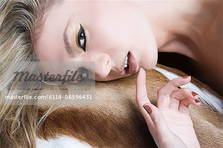 Woman leaning on animal skin Stock Photo - Premium Royalty-Free, Image code: 6114-06596431