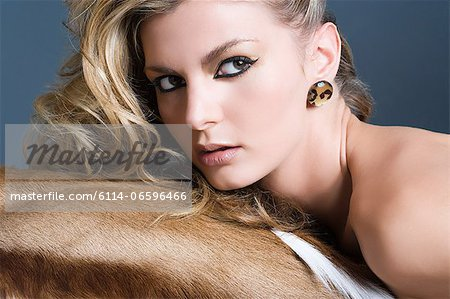 Woman leaning on animal skin Stock Photo - Premium Royalty-Free, Image code: 6114-06596466