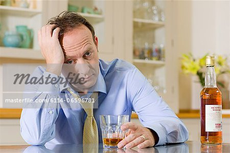 Stressed man with whisky Stock Photo - Premium Royalty-Free, Image code: 6114-06596781