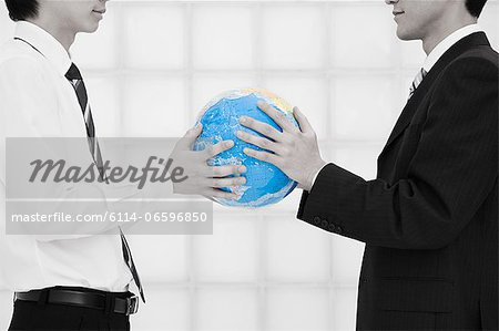 Office workers holding globe Stock Photo - Premium Royalty-Free, Image code: 6114-06596850