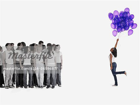 Woman holding balloons Stock Photo - Premium Royalty-Free, Image code: 6114-06596877