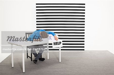 Office worker with sign that says help Stock Photo - Premium Royalty-Free, Image code: 6114-06597047