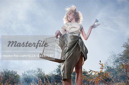 Girl with a bird and cage Stock Photo - Premium Royalty-Free, Image code: 6114-06597087