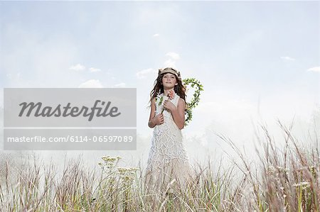Girl dressed as fairy in field with flower Stock Photo - Premium Royalty-Free, Image code: 6114-06597089