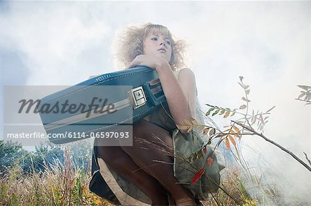 Girl with a suitcase Stock Photo - Premium Royalty-Free, Image code: 6114-06597093