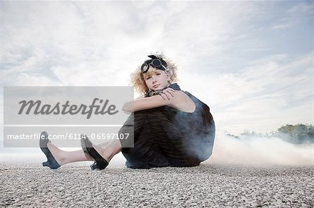 Girl wearing goggles and sitting on road Stock Photo - Premium Royalty-Free, Image code: 6114-06597107
