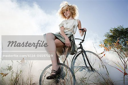Girl sitting on bicycle Stock Photo - Premium Royalty-Free, Image code: 6114-06597109