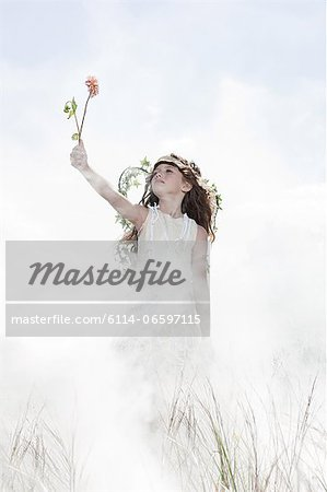 Girl dressed as fairy with flower Stock Photo - Premium Royalty-Free, Image code: 6114-06597115