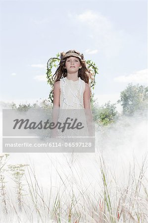Girl dressed as fairy in cloud of smoke Stock Photo - Premium Royalty-Free, Image code: 6114-06597128