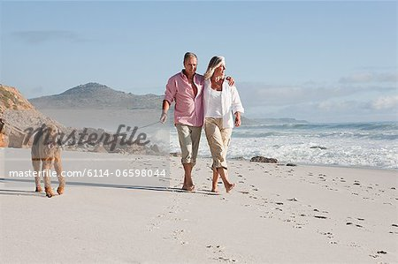Couple walking dog by the sea Stock Photo - Premium Royalty-Free, Image code: 6114-06598044