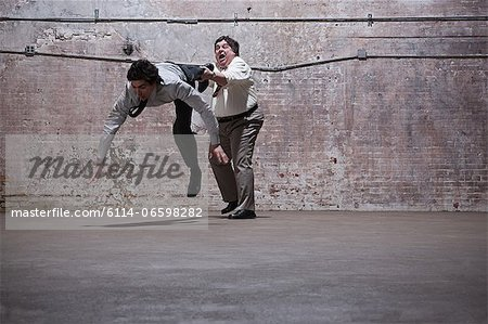People fighting in warehouse Stock Photo - Premium Royalty-Free, Image code: 6114-06598282