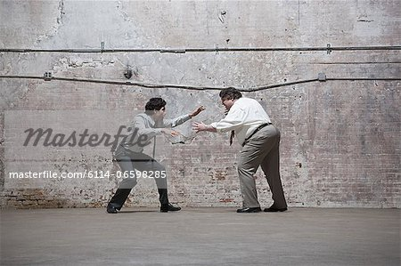 People fighting in warehouse Stock Photo - Premium Royalty-Free, Image code: 6114-06598285