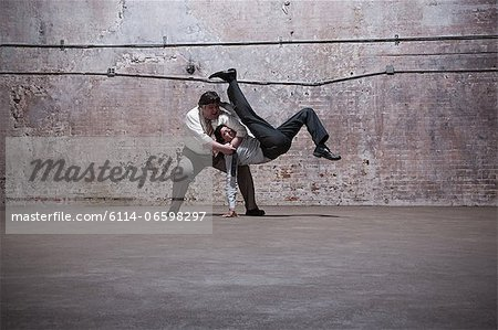People fighting in warehouse Stock Photo - Premium Royalty-Free, Image code: 6114-06598297