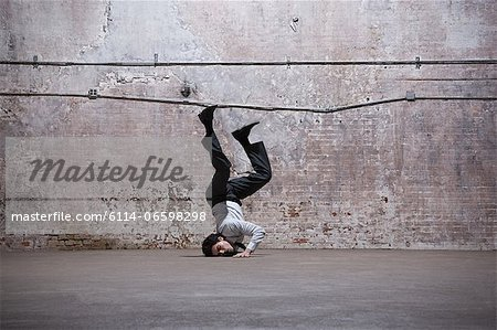 Man falling on head in warehouse Stock Photo - Premium Royalty-Free, Image code: 6114-06598298