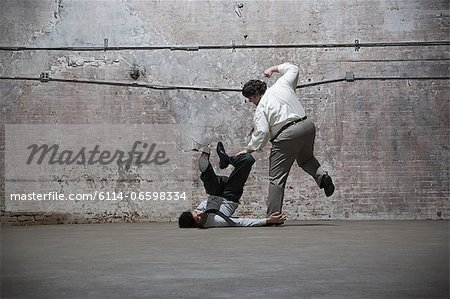 People fighting in warehouse Stock Photo - Premium Royalty-Free, Image code: 6114-06598334