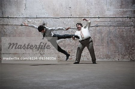 People fighting in warehouse Stock Photo - Premium Royalty-Free, Image code: 6114-06598336