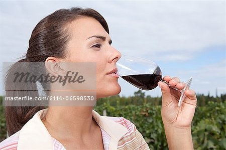Woman drinking wine in vineyard Stock Photo - Premium Royalty-Free, Image code: 6114-06598530